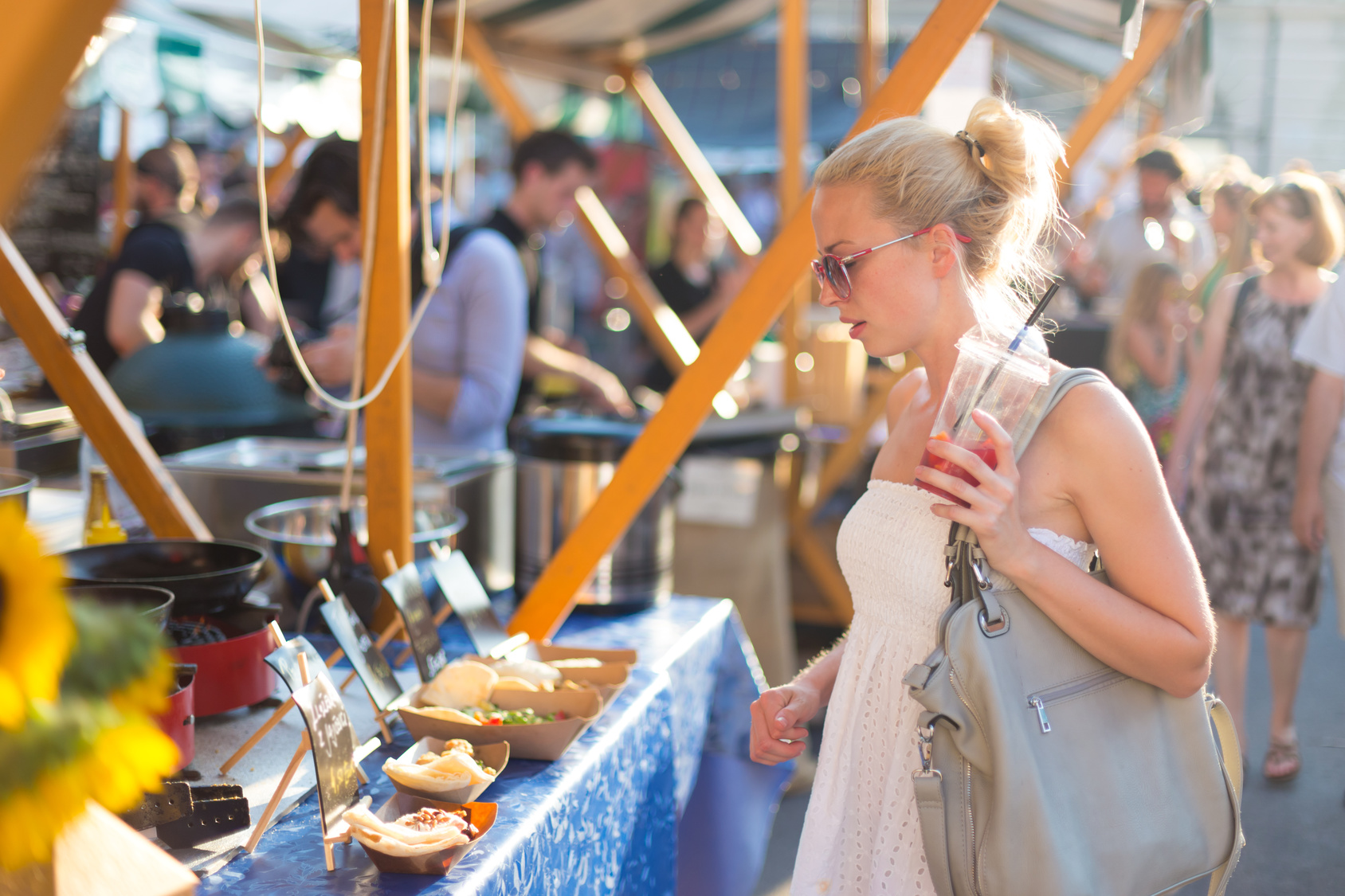 Женщина покупает еду на фестивале уличной еды.