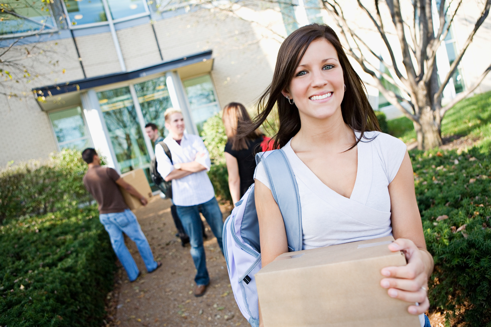 College-Girl-Smiling-Holding-Box-Walking-Outside