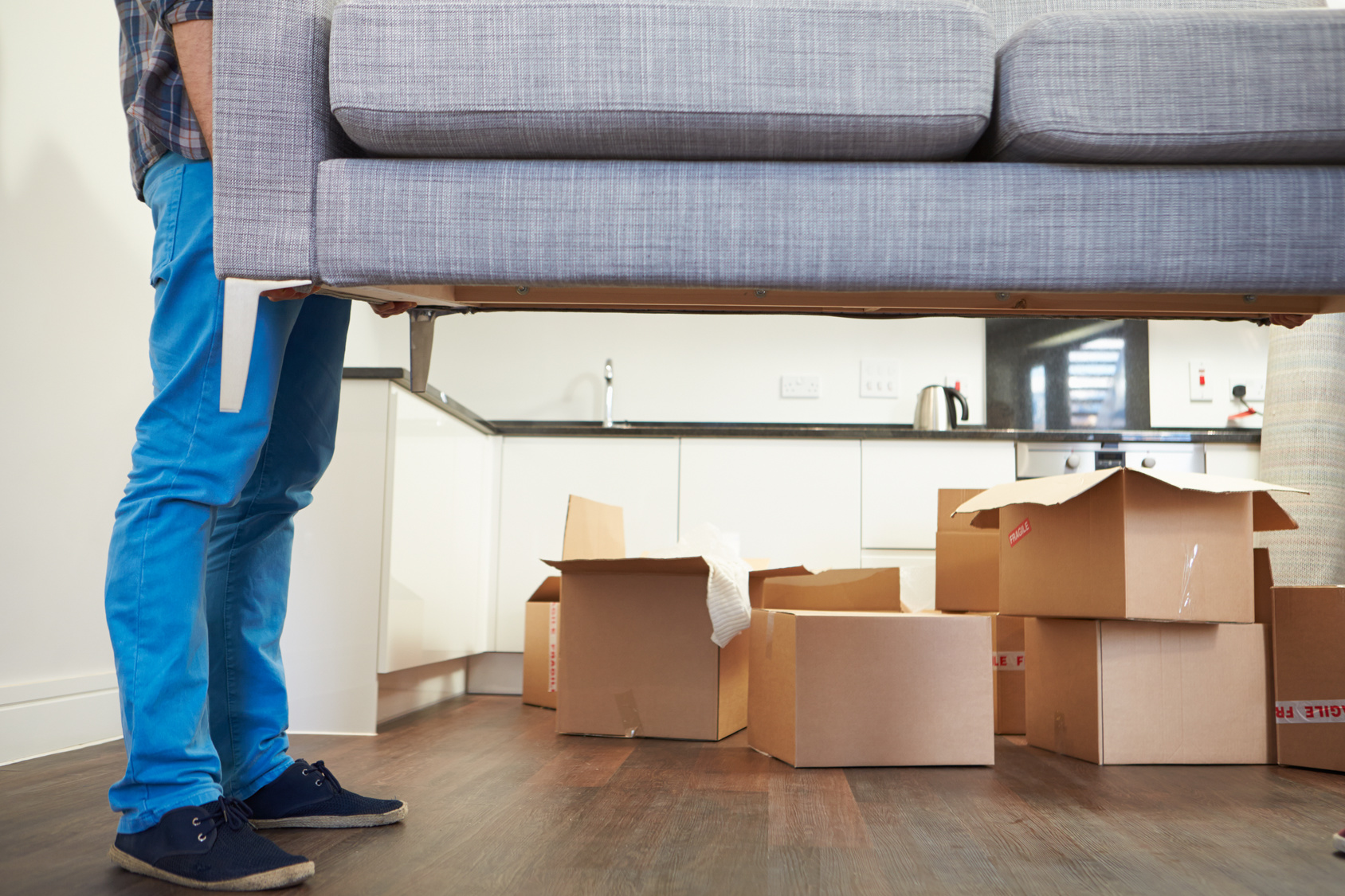 Man-Carrying-Sofa-When-Moving-into-New-House