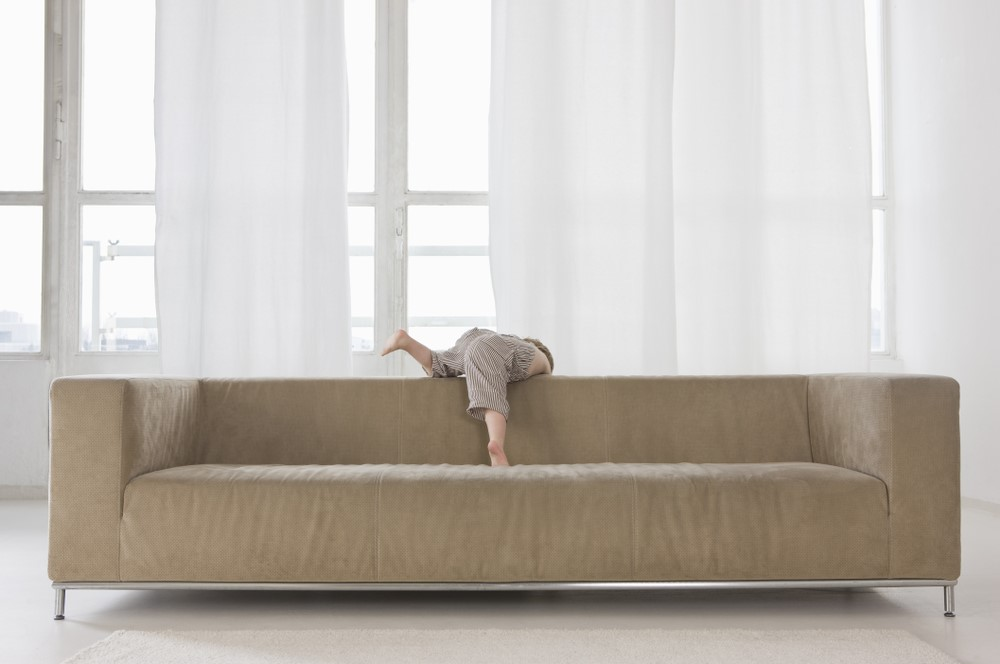 Child Hanging Off Back of Couch
